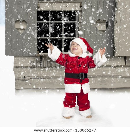 snowing on little child in santa clothes, seated in the snow - stock photo