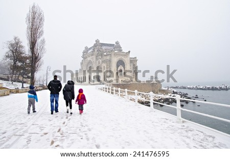 Snowing on the shore at the Black Sea, in Constanta, Romania. Casino building is at the background. - stock photo