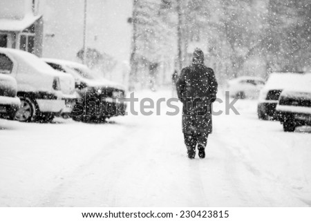 Snowing urban landscape with people passing by  - stock photo
