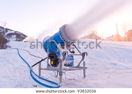 """Snowmaking is the production of snow by forcing water and pressurized air through a """"snow gun"""" or """"snow cannon"""", on ski slopes. Snowmaking is mainly used at ski resorts to supplement natural snow. - stock photo"""