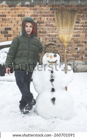 Snowman and child in the yard. Winter - stock photo