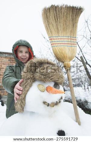 Snowman and child in the yard. Winter