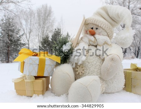Snowman and gift boxes with bows in snow in the winter forest - stock photo
