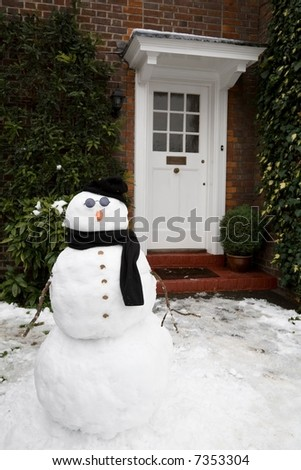 Snowman and house - stock photo