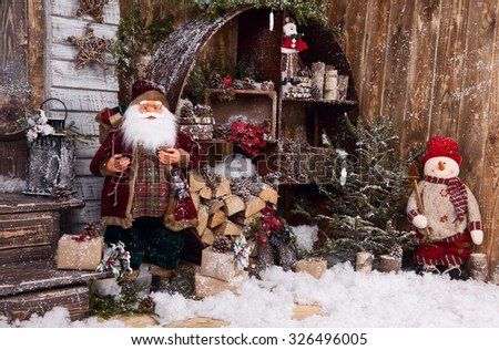 Snowman and Santa Claus toy in winter decor - stock photo