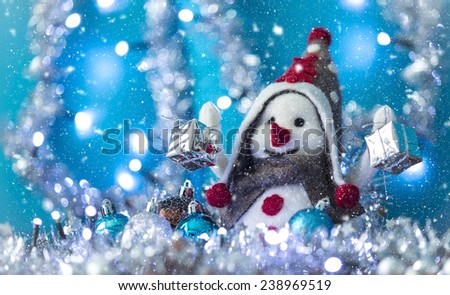 Snowman between Christmas balls smiling brought Christmas gifts, turquoise background with flashing lights snowing - stock photo