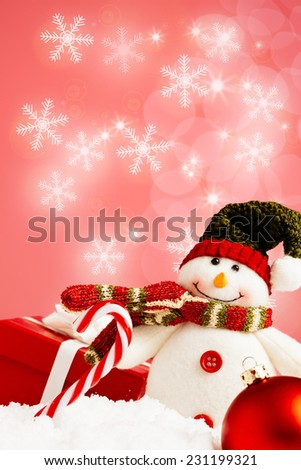 Snowman, christmas present and candy cane and a red bauble on a red background with snowflakes - stock photo