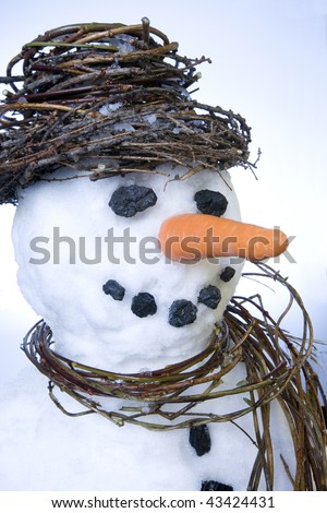 Snowman close-up with scarf and hat made from natural plant materials and a white snow background. - stock photo