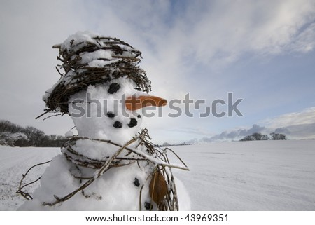 Snowman close-up with scarf and hat made from natural plant materials in a snowy field with blue sky. - stock photo
