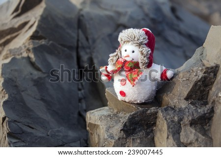 Snowman  in winter hat on the rocks in tropical place. - stock photo