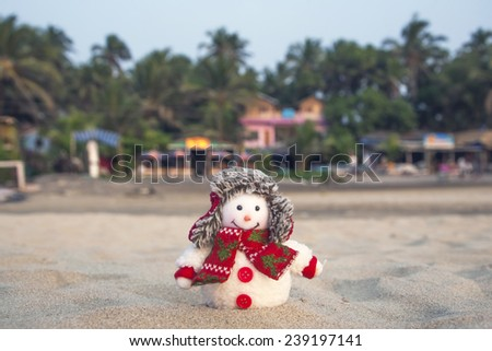 Snowman in winter hat on the tropical beach. - stock photo
