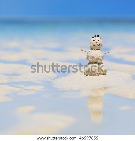 Snowman made from white tropical sand on exotic beach with ocean on background.