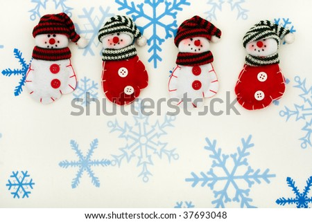 Snowman  mittens sitting together on a snowflake background, happy holidays
