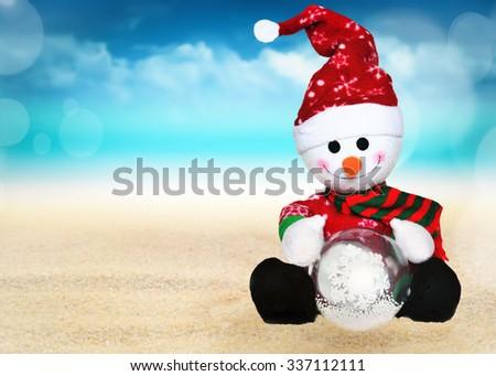Snowman on the summer beach. Merry Christmas. - stock photo