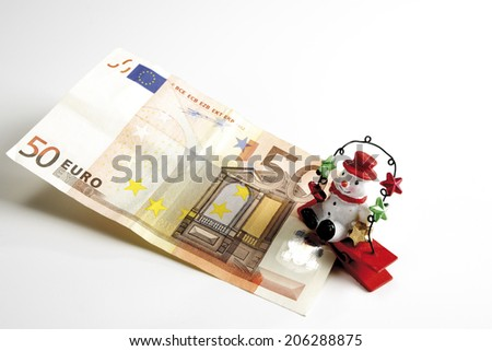 Snowman sitting on Euro notes, elevated view - stock photo