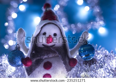 Snowman smiling brought Christmas balls, turquoise background with flashing lights - stock photo