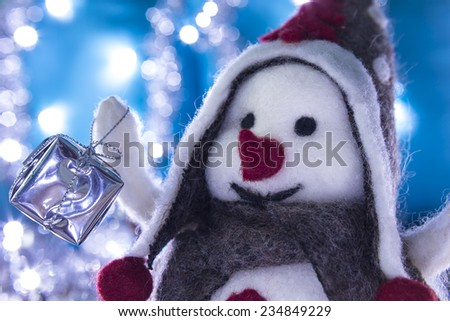 Snowman smiling brought Christmas gifts, turquoise background with flashing lights - stock photo