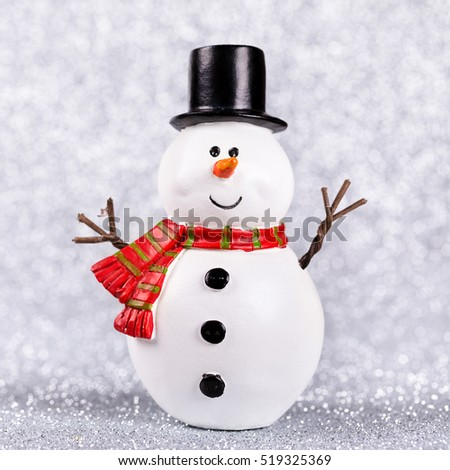 Snowman toy on shiny silver background.  Christmas and New Year decoration