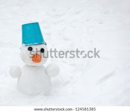 Snowman with blue bucket on the head - stock photo