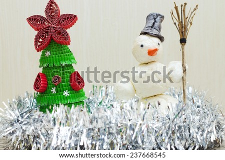 Snowman with broom in hand near Christmas tree - stock photo