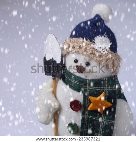 Snowman with shovel and scarf in a wintery scene with snowfall. - stock photo