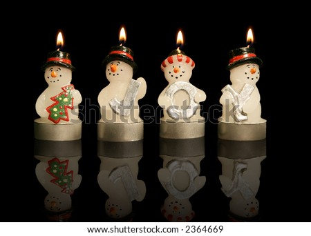 Snowmen candles holding letters spelling out joy - stock photo