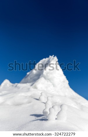 Snowmen climbing up a icy mountain, concept business promotion and success - stock photo