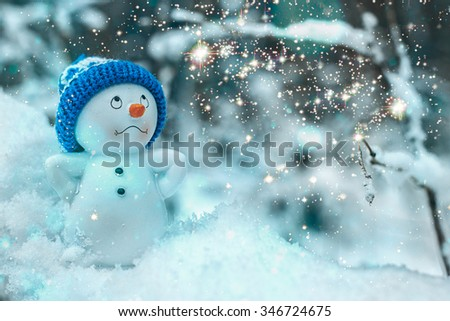 SNOWMEN SERIES: Close Up Of Little Cute Toy Snowman With Wearing Hat And Carrot Nose Standing In The Snow And Gazing at Shining Magic Stars, Snowman With Lights On Frozen Winter Christmas Background