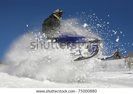 snowmobile rider jumping through snow - stock photo