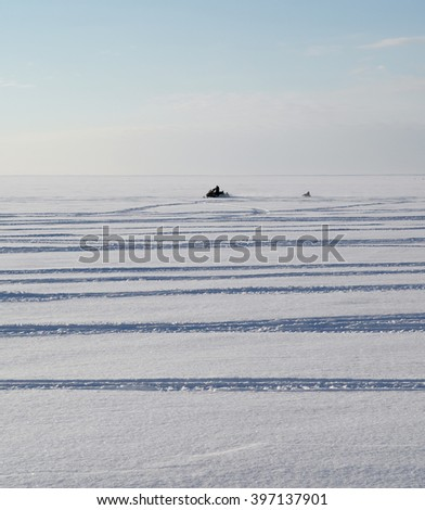 Snowmobile tows a tube behind. Sunny winter day, frosty weather, a lot of space and skyline after. - stock photo