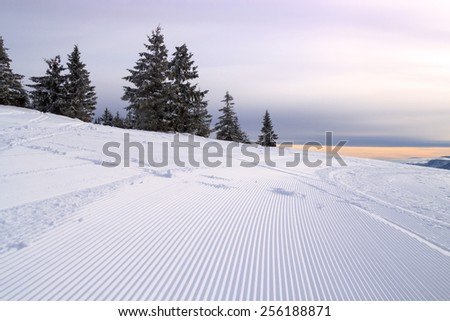 snowmobile tracks on a hillside on a clear day - stock photo