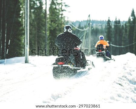 Snowmobiles are accelerating in the sunshine. Image has a vintage effect.