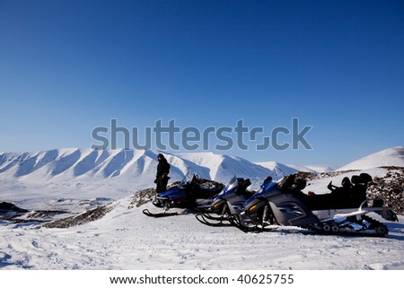 Snowmobiles in a barren winter landscape, Svalbard, Norway