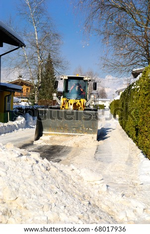 Snowplow cleaning streets in austria after heavy snow storm. - stock photo