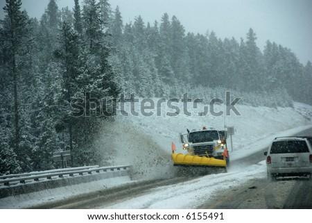 Snowplow clearing road in snowstorm,		Rocky Mountains,	Idaho - stock photo