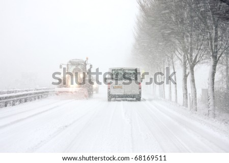 Snowplow driving in snowstorm in the Netherlands - stock photo