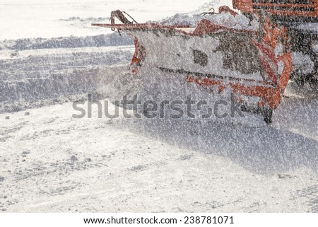 Snowplow removing snow from city road - stock photo