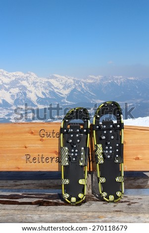 Snowshoe on bench with Alps - stock photo
