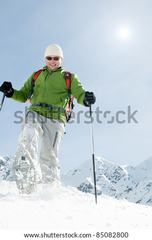 Snowshoeing - man trekking in winter mountains (copy space, cover)