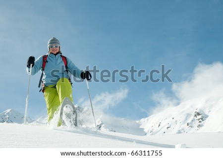 Snowshoeing - woman trekking in winter mountains - space for text - stock photo