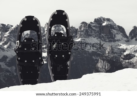 Snowshoes in snow at mountain peak, nice sunny winter day - stock photo