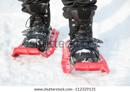 Snowshoes. Snowshoeing closeup. Red new modern high-end snowshoes. Man hiking in snow on snowy winter day. - stock photo