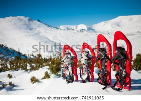 Snowshoes standing in the snow against the background of snow and mountains. Winter walks with forests and mountains.