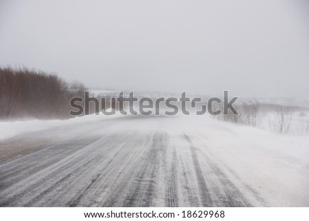 Snowstorm, slick roads and go the machines - stock photo