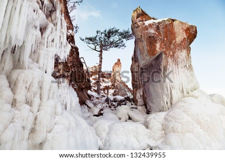 Snowy and icy rocks at the coastline, sunny day. - stock photo