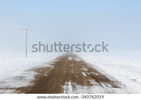 snowy foggy road - stock photo