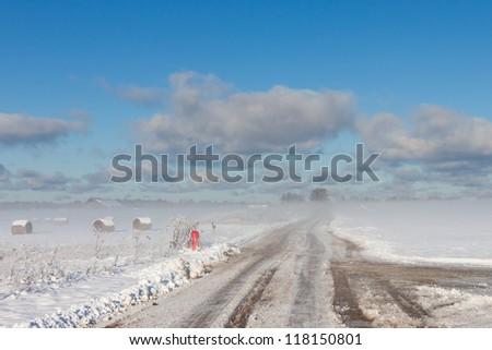 snowy hay bales with road near farm (fog) - stock photo
