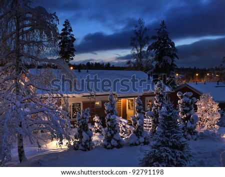 Snowy house on Christmas winter evening blue moment - stock photo