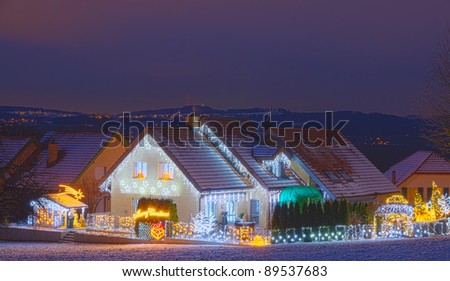 snowy houses at night fully decorated with christmas lights - stock photo