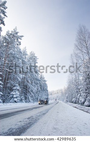 Snowy land road at winter and coming car, deep blue sky - stock photo